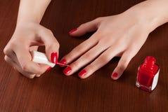 Hembra que aplica esmalte de uñas del color rojo en el escritorio de madera Imagen de archivo libre de regalías