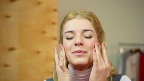 Hembra que aplica la crema antienvejecedora costosa, disfrutando del efecto de piel que alisa metrajes