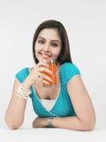 Hembra que bebe el zumo de naranja Imagen de archivo