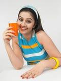 Hembra que bebe el zumo de naranja Imagen de archivo libre de regalías