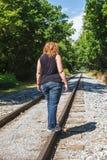 Hembra que camina los carriles en vía del tren Foto de archivo