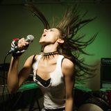 Hembra que canta en el mic. Foto de archivo libre de regalías