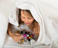 Hembra que come los dulces en cama Fotos de archivo libres de regalías