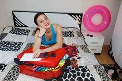 Hembra que consigue lista para viajar mujer hermosa joven, maleta roja, sentada, esperando, vacaciones de verano, AR colorida, qu fotos de archivo libres de regalías