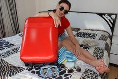Hembra que consigue lista para viajar mujer hermosa joven, maleta roja, sentada, esperando, vacaciones de verano, AR colorida, qu fotografía de archivo libre de regalías