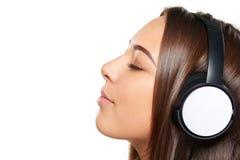 Hembra que escucha disfrutando de música en auriculares con los ojos cerrados Foto de archivo
