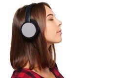 Hembra que escucha disfrutando de música en auriculares con los ojos cerrados Imágenes de archivo libres de regalías