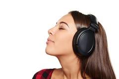Hembra que escucha disfrutando de música en auriculares con los ojos cerrados Fotografía de archivo