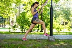 Hembra que hace el ejercicio con las correas del trx de la aptitud en un parque del verano Foto de archivo