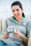 Hembra que juega los videojuegos que concentran en el sofá Imágenes de archivo libres de regalías