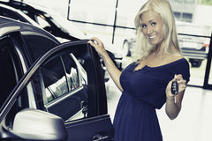 Hembra que lleva a cabo llaves del coche delante de los nuevos coches Foto de archivo libre de regalías