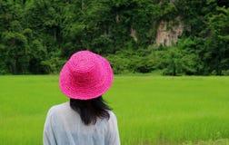 Hembra que lleva a Straw Hat Looking rosado vivo en el campo verde vibrante del arroz, estación de lluvias fotografía de archivo libre de regalías