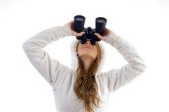 Hembra que mira hacia arriba con binocular Fotos de archivo libres de regalías