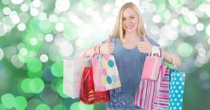 Hembra que muestra los pulgares para arriba mientras que lleva los panieres coloridos Foto de archivo libre de regalías