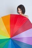 Hembra que oculta sobre el paraguas del arco iris Imágenes de archivo libres de regalías