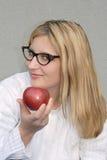 Hembra que ofrece una manzana Foto de archivo libre de regalías