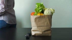 Hembra que pone el bolso con las verduras en una tabla almacen de metraje de vídeo