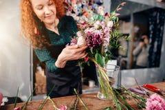 Hembra que pone las flores agradables en florero en tienda del ` s del florista Fotografía de archivo