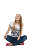Hembra que se sienta con las piernas cruzadas en el suelo que mira para arriba Imagen de archivo libre de regalías