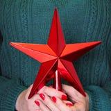 Hembra que sostiene la estrella roja de la Navidad disponible para el árbol de los chistmas de los tops Cierre para arriba Feliz  Imagen de archivo