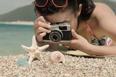 Hembra que toma una foto de los accesorios del verano en la playa Imagenes de archivo