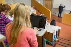 Hembra que usa el ordenador portátil con los estudiantes y el profesor en la sala de conferencias Fotografía de archivo libre de regalías