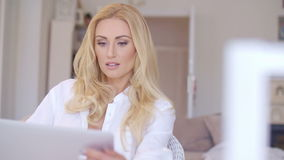 Hembra rubia atractiva en blanco usando su ordenador portátil almacen de metraje de vídeo