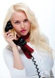 Hembra rubia bastante joven en el teléfono viejo Imagenes de archivo