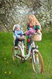 Hembra rubia con la bicicleta de la ciudad con el bebé en silla de la bicicleta Imagen de archivo libre de regalías