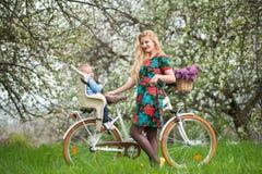 Hembra rubia con la bicicleta de la ciudad con el bebé en silla de la bicicleta Imágenes de archivo libres de regalías