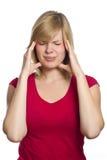 Hembra rubia que tiene un dolor de cabeza fotos de archivo
