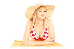 Hembra rubia sonriente con el sombrero que miente en una toalla y una presentación de playa Fotos de archivo
