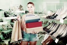 Hembra satisfecha del adolescente que sostiene las cajas en boutique de los zapatos Foto de archivo