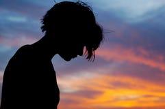 Hembra silueteada delante del cielo de la puesta del sol Foto de archivo