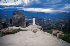 Hembra sola en la tela escocesa blanca al borde de la mirada de la roca en los monasterios de Meteora Hembra en la roca y los mon Foto de archivo libre de regalías