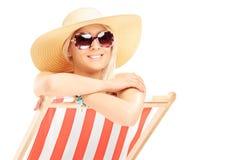 Hembra sonriente de los jóvenes con un sombrero que presenta en una silla de playa Foto de archivo