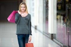 Hembra sonriente en alameda de compras que camina con las bolsas de papel Imágenes de archivo libres de regalías