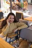 Hembra sonriente en el café que habla sobre el teléfono móvil Imagen de archivo libre de regalías