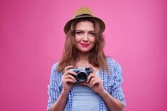 Hembra sonriente en la camisa comprobada que sostiene una cámara retra Imagenes de archivo