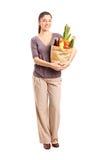 Hembra sonriente que sostiene un bolso lleno de tiendas de comestibles Fotos de archivo libres de regalías