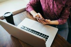 Hembra usando el teléfono y el ordenador portátil en un café imagen de archivo libre de regalías
