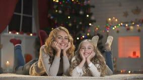 Hembra y muchacha que mienten debajo del árbol de navidad, mirando a la cámara y sonriendo, decoración almacen de metraje de vídeo