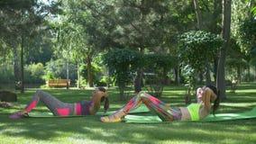 Hembras activas de la aptitud que hacen sentar-UPS en la estera de la yoga