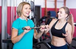 Hembras de diverso entrenamiento de la fuerza de la edad en gimnasio imagenes de archivo