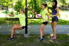 Hembras deportivas que hacen ejercicios con las correas del trx de la aptitud Imágenes de archivo libres de regalías