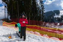Hembras jovenes en los trajes de esquí que se colocan cerca de la cerca en un esquí-reso Foto de archivo libre de regalías