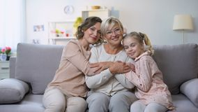 Hembras multigeneraciones que abrazan en la cámara sonriente del sofá casero, proximidad de la familia metrajes