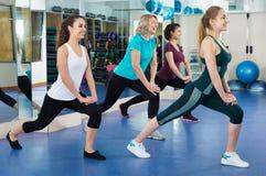 Hembras positivas que se resuelven en la clase aerobia en gimnasio moderno Imágenes de archivo libres de regalías