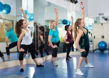 Hembras positivas que se resuelven en la clase aerobia en gimnasio moderno fotos de archivo