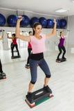 Hembras que hacen aeróbicos del paso en gimnasio Imágenes de archivo libres de regalías